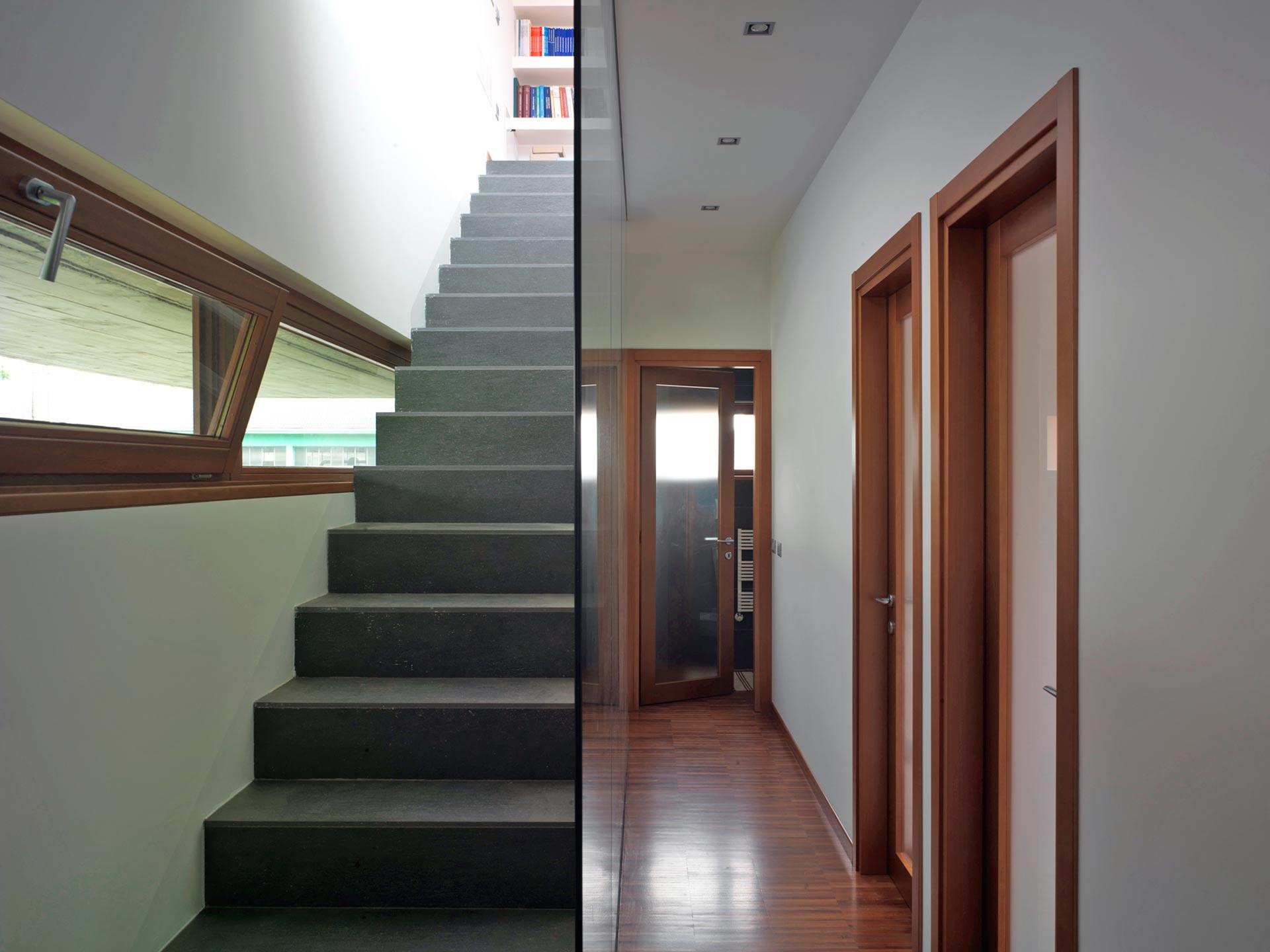 Vista di un corridoio e di una scala con finestre a nastro ad apertura a vasistas