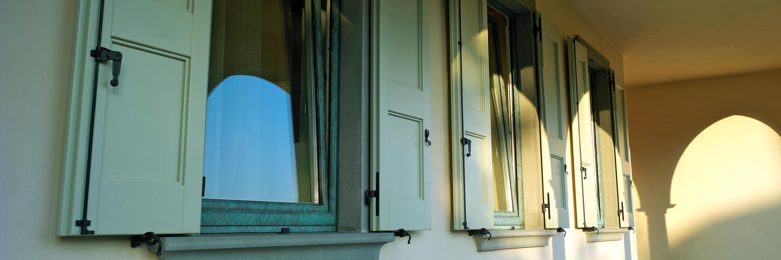 Vista esterna di tre finestre Alu 90 Bronze con scuri in legno laccati